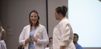 Heather Raley, left, receives her white coat from Sara Robertson, director of the University of Louisville doctor of nursing practice program, during a ceremony on Aug. 16 at the UofL Health Sciences Center.