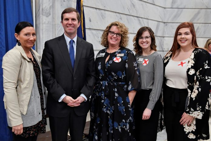 UofL researchers joined Gov. Andy Beshear at a Jan. 7 Capitol Rotunda news conference to raise human trafficking awareness. UofL graduate students Tara Sexton, Emily Edwards and Victoria Dobson are shown with Jennifer Middleton (center), associate professor of social work and director of the Human Trafficking Research Institute. Credit Timothy D. Easley.